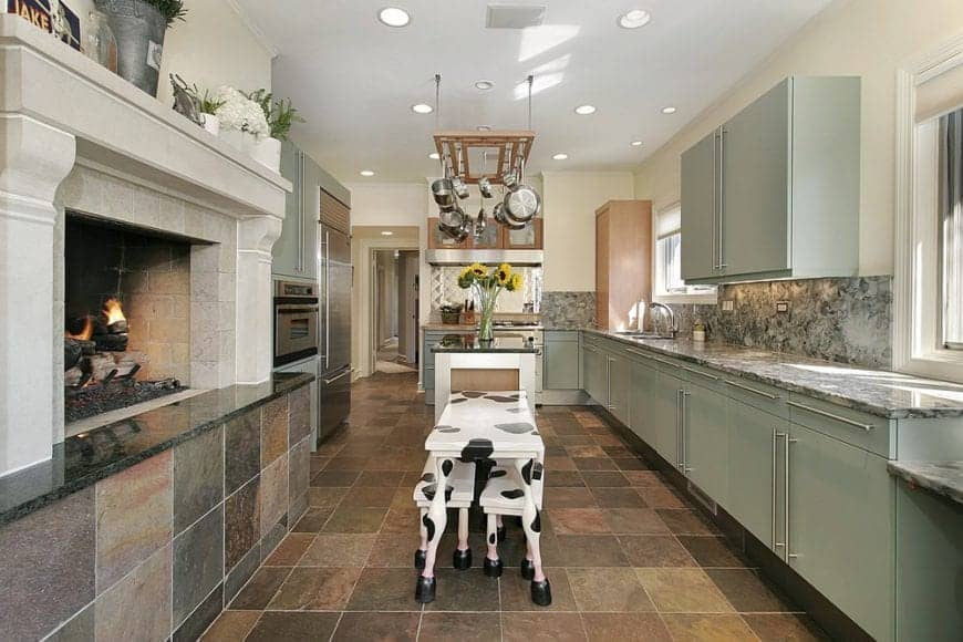 Farmhouse kitchen with limestone flooring and white ceiling mounted with recessed lighting and a hanging pot rack suspended over the kitchen island with attached cow print dining set.