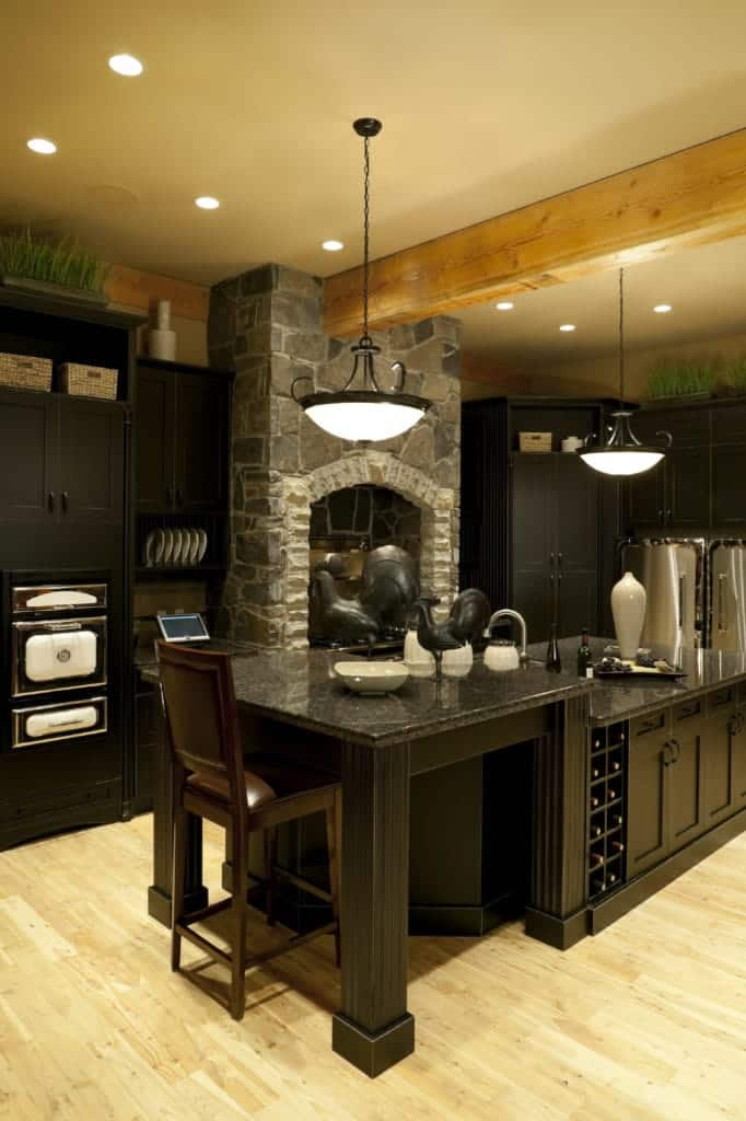 Wrought iron pendants hang over the two-tier breakfast island fitted with storage and double column wine rack in this kitchen with wood beam ceiling and light wood plank flooring. It has a stone brick fireplace fixed in between black cabinetry.