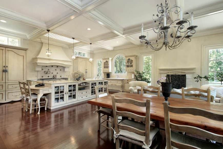 An open kitchen showcases white cabinetry and an island bar fitted with glass front cabinets. It is lighted by clear glass pendants that hung from the coffered ceiling.