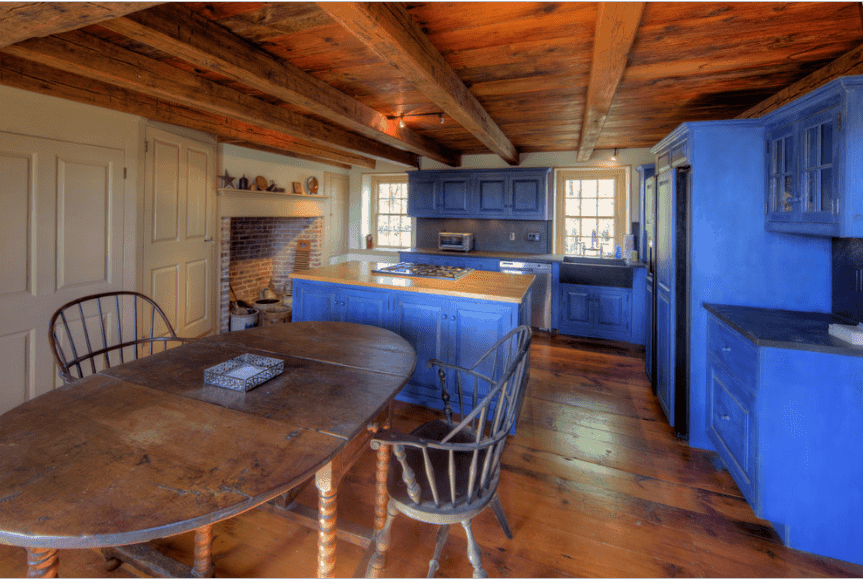 An all wood kitchen with blue cabinetry and round dining set along with a red brick fireplace lined with a white mantel.