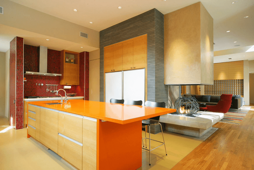 Lively kitchen boasts an orange breakfast island fitted with a sink and wooden storage along with a unique three-sided fireplace and stainless steel vent hood fixed to the red brick wall.
