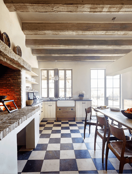 A dine-in kitchen with a stone brick fireplace lined with a mantel that's topped with decorative ceramic plates. It has checkered flooring and wood beam ceiling with a hanging pendant light.