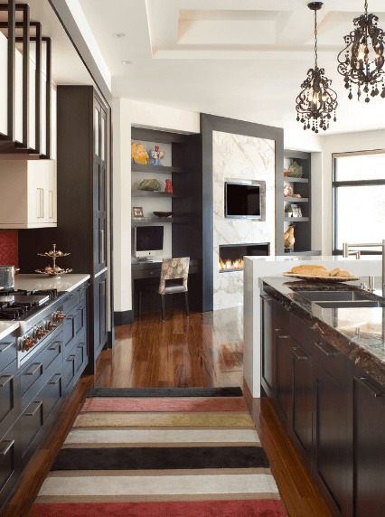 Luxury kitchen illuminated by a pair of vintage pendants that hung from the coffered ceiling. It has a modern fireplace and rich hardwood flooring topped with a striped multi-colored kitchen runner.