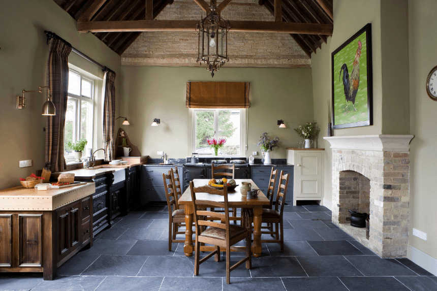 Farmhouse kitchen decorated with a lovely rooster wall art mounted above the stone brick fireplace. It has blue cupboards and wooden dining set lighted by a glass pendant that hung from the cathedral ceiling.