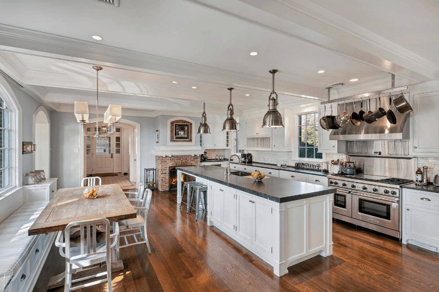 White gourmet kitchen with a breakfast nook by the window. It includes a red brick fireplace and an island bar topped with black granite counter and lighted by chrome pendants.