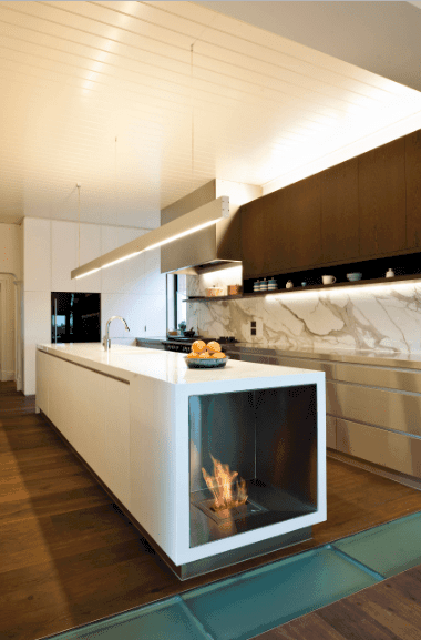 Modern kitchen with a sleek white island bar fitted with a fireplace on its end. It is illuminated by a linear pendant that hung from the white shiplap ceiling.