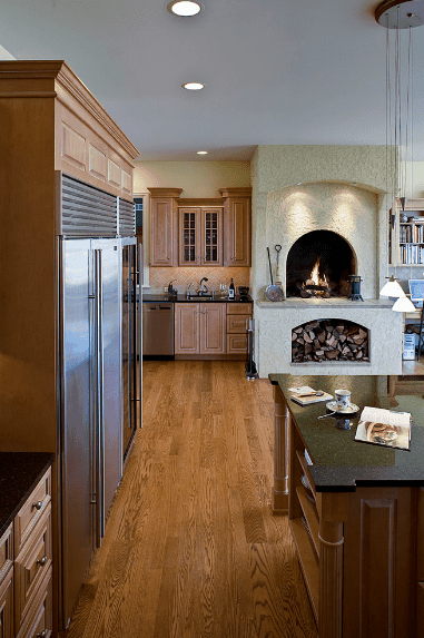 This kitchen features an arched fireplace with firewood storage underneath. It includes wooden cabinetry and stainless steel appliances.