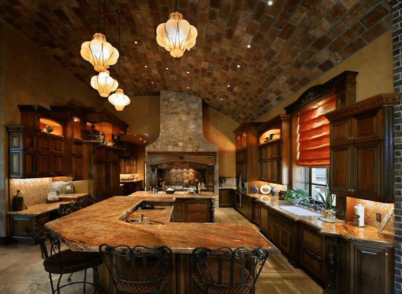 Warm kitchen showcases dark wood cabinetry along with two-tier breakfast counter and a kitchen island that sits next to the stone fireplace. It is lighted by lovely pendants that hung from the curved brick ceiling.