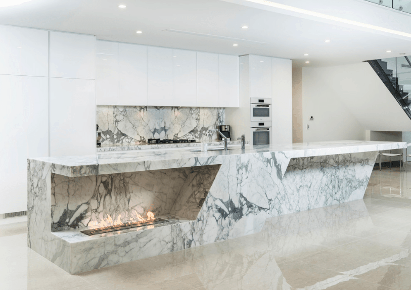 Minimalist kitchen boasts sleek white cabinetry accented with marble backsplash that matches with the lengthy island bar fitted with a modern fireplace.