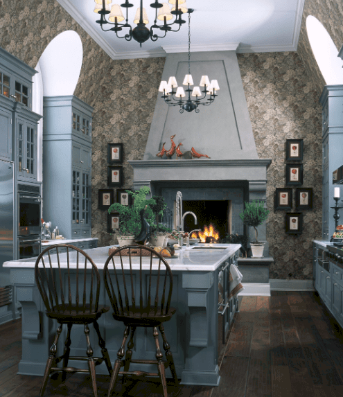 Magnificent kitchen with a central breakfast island paired with round back counter chairs and surrounded with soft blue cabinetry. It has a fireplace with small black framed wall arts on its sides.