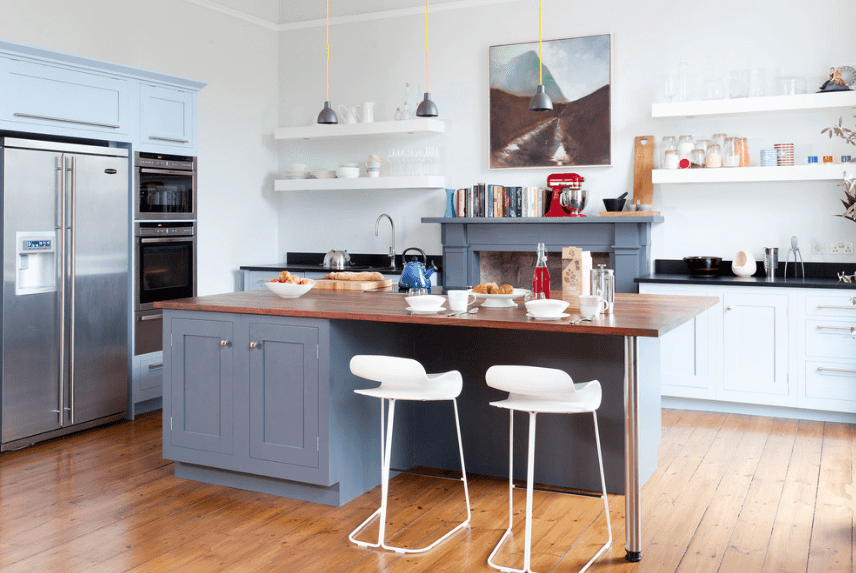 White bar stools sit at the blue breakfast island in this kitchen showcasing white cupboards and floating shelves with a fireplace in the middle.
