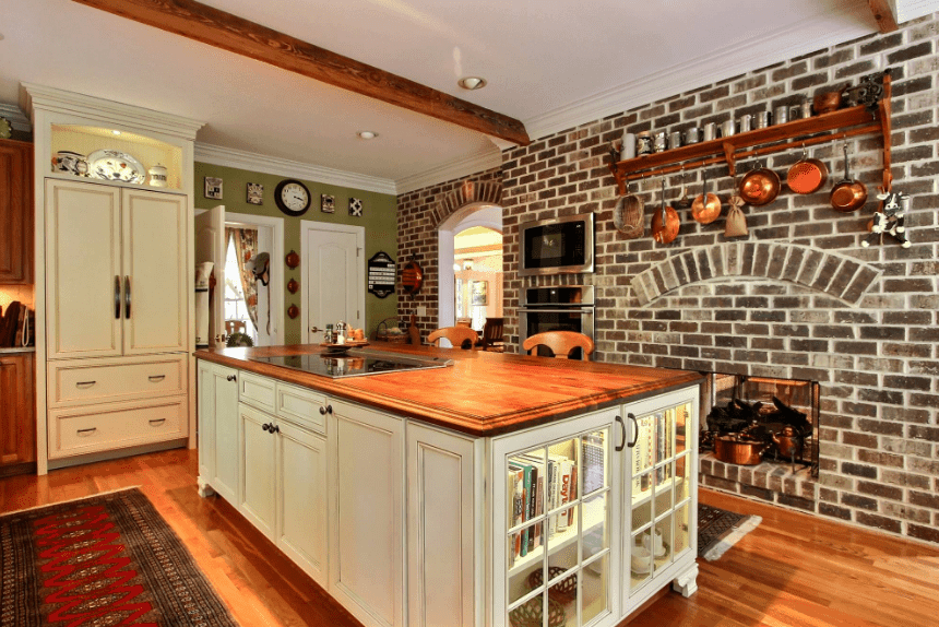 Traditional kitchen features white cabinet and breakfast island topped with a wooden counter and modern cooktop. It has a wall oven and fireplace fixed to the brick wall.