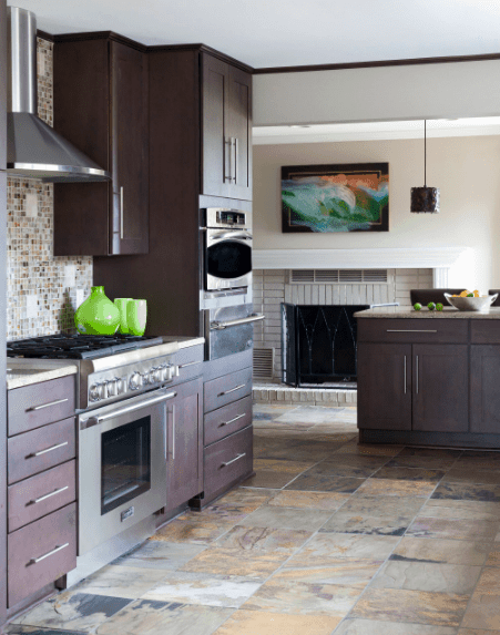 This kitchen is decorated with a lovely wall art that hung above the white fireplace covered with a wrought iron fence. It has dark wood cabinetry and kitchen bar over limestone flooring.