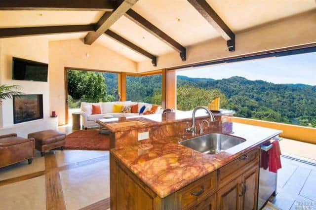 An open kitchen with a wooden two-tier breakfast island and white fireplace with leather seating. It includes a vaulted ceiling with exposed wood beams and panoramic windows overlooking a spectacular hills view.