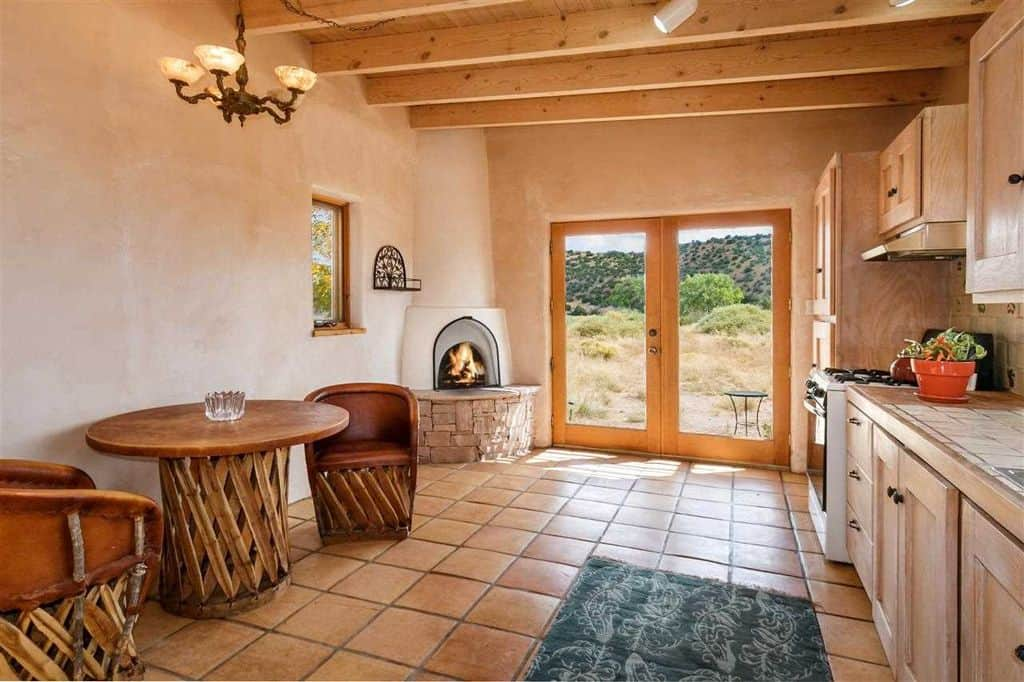 This kitchen offers a terracotta flooring and wood beam ceiling along with a kiva fireplace in the corner next to the glass door. It includes a round wooden dining set lighted by a vintage chandelier.