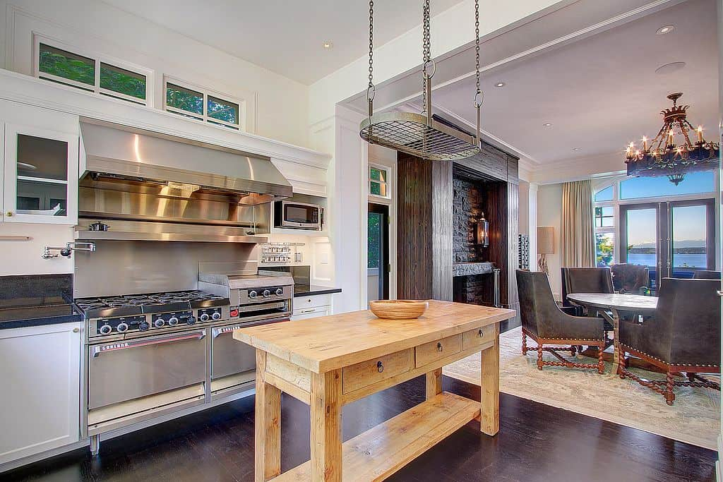 A dine-in kitchen boasts a metal pot rack that hung over a light wood kitchen island topped with a wooden bowl. It includes classy dining set by the fireplace illuminated by an elegant chandelier.