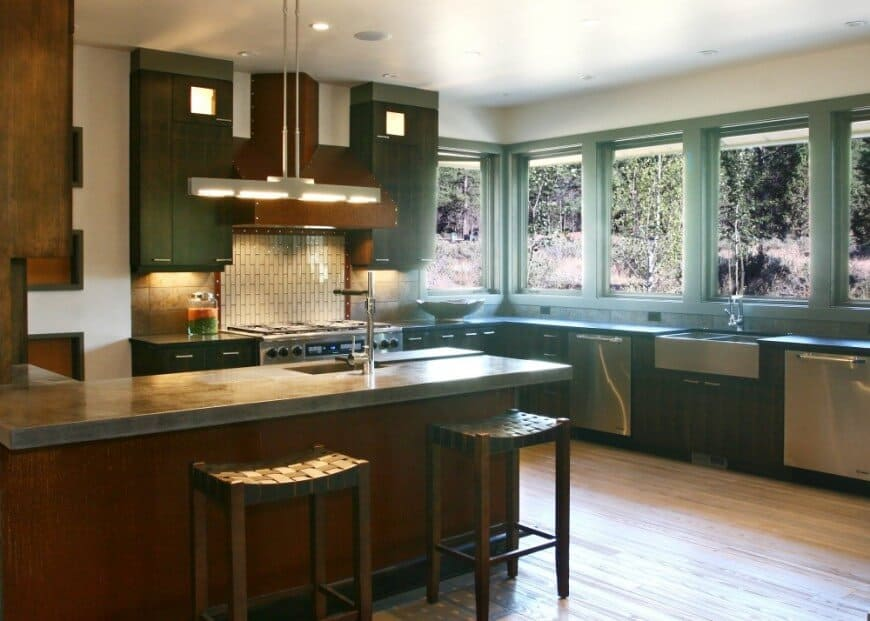 This kitchen features sage green paneled windows and cabinetry. It also has a wood peninsula topped with concrete counter and lighted by a linear pendant.