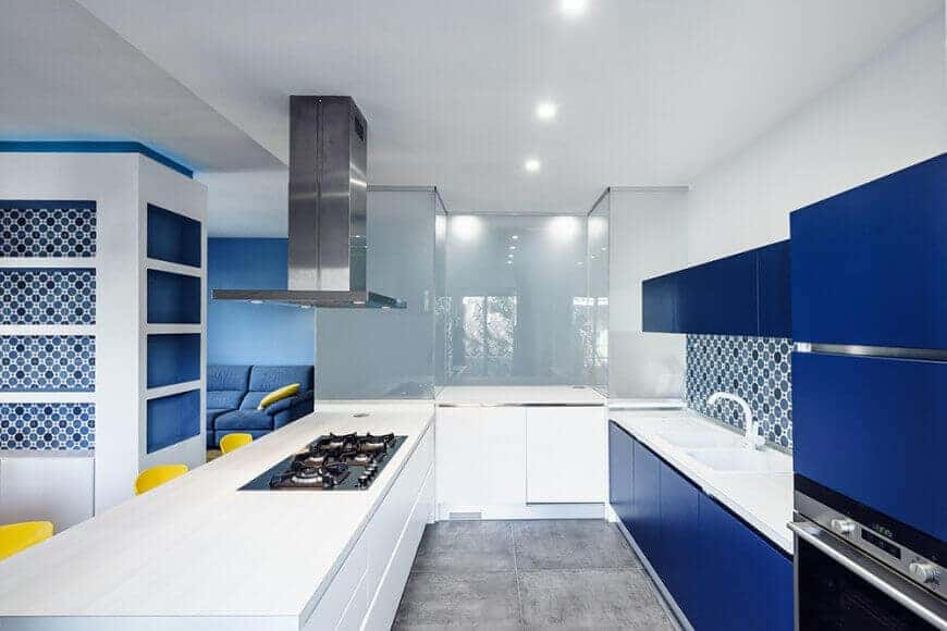 Modern kitchen accented with vibrant blue cabinetry and lovely patterned backsplash. It has white peninsula fitted with a cooktop underneath a stainless steel vent hood.