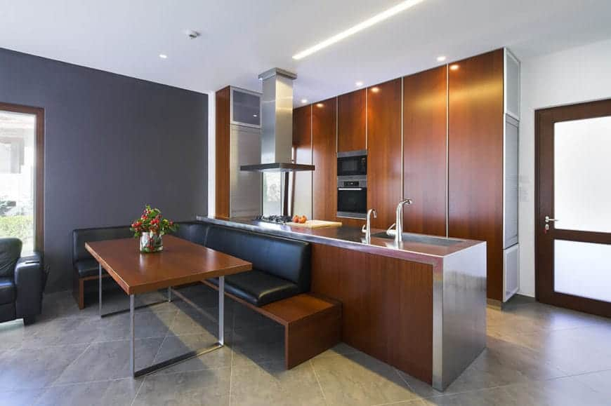 Elegant kitchen boasts rich wood cabinetry and stainless steel countertop. There's an L-shaped wooden bench fitted with black leather cushion fixed on the gray wall and peninsula.