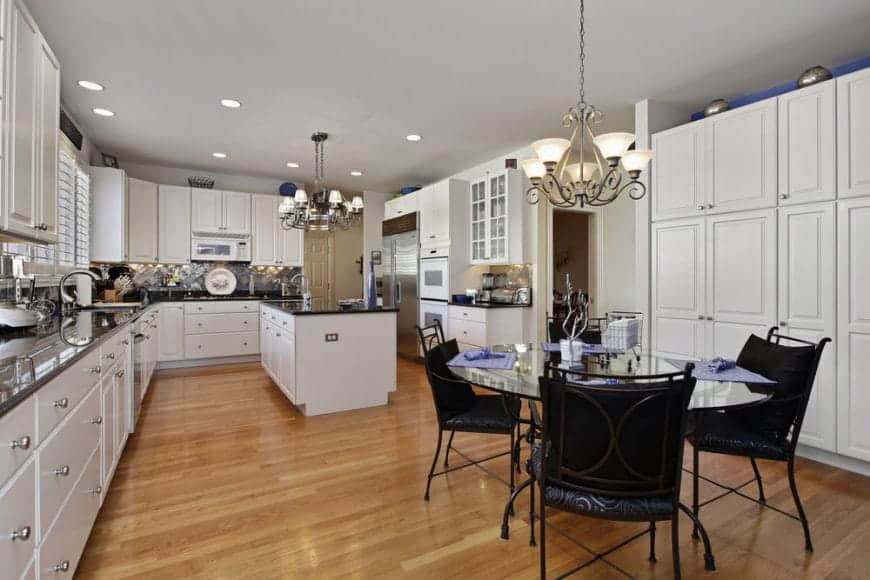 Huge white kitchen contrasted with black granite countertop and black cushioned chairs that surround a round glass dining table. It features hardwood flooring and lighted by vintage chandeliers.