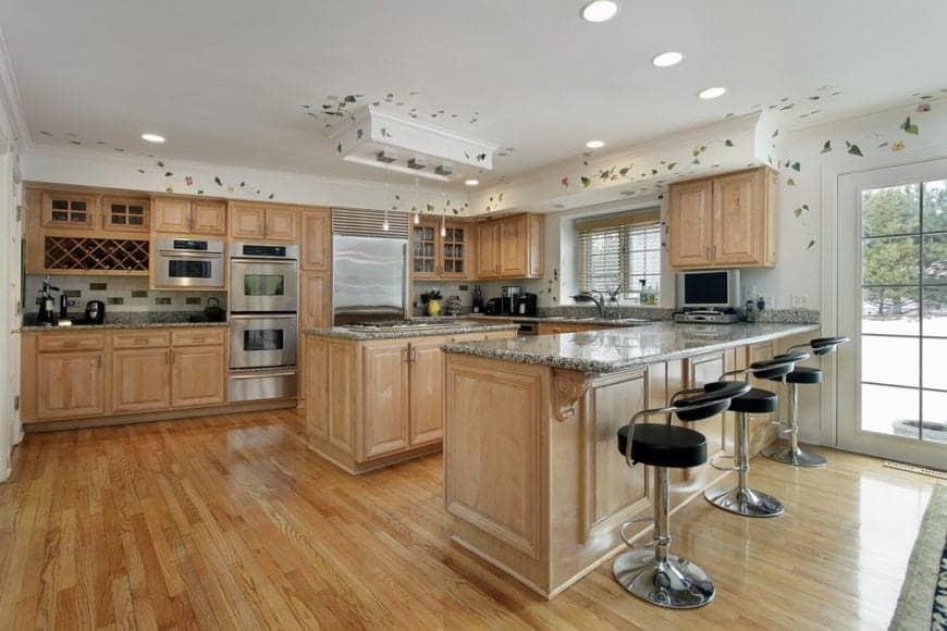 Kitchen with light wood cabinetry and a breakfast island situated across the peninsula aligned with black bar stools.