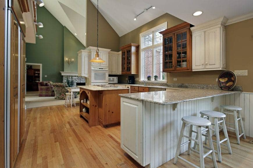 Marvelous kitchen accented with geometric walls and a combination of white and wood cabinetry. Round gray chairs sit on a white shiplap peninsula over hardwood flooring.
