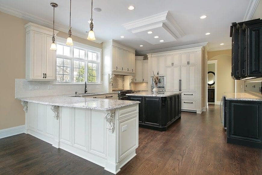 Sophisticated kitchen features white and black cabinetry over hardwood flooring. It has a gray marble top peninsula illuminated by pendant lights and contrasted by a black center island.
