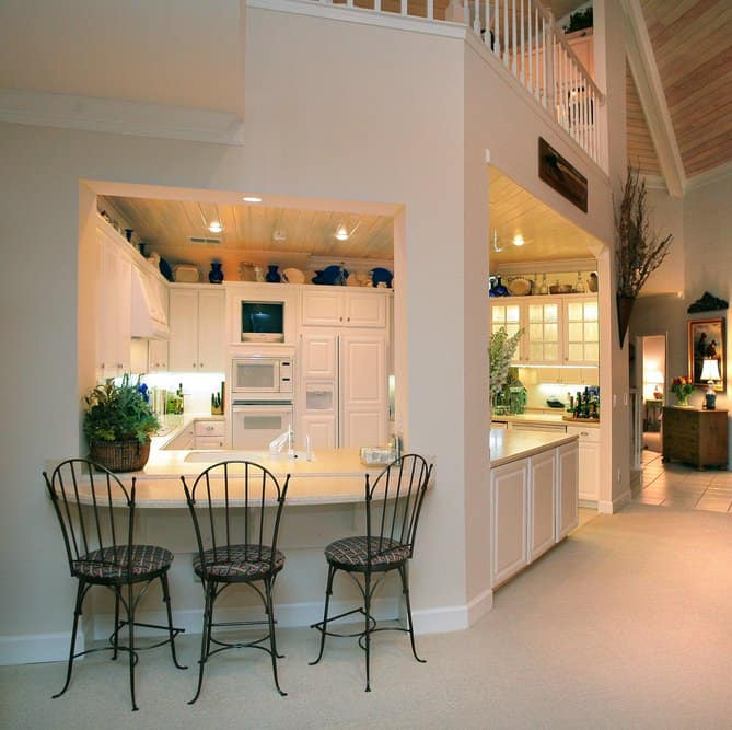 A covered kitchen boasts light wood plank ceiling fitted with recessed lighting. It is designed with decorative dinnerware atop white cabinetry.