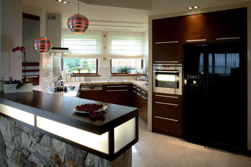 Kitchen with wood cabinetry and a dark peninsula with built-in lighting and stone body. It has glass windows covered with white roman shades placed above the marble counter.