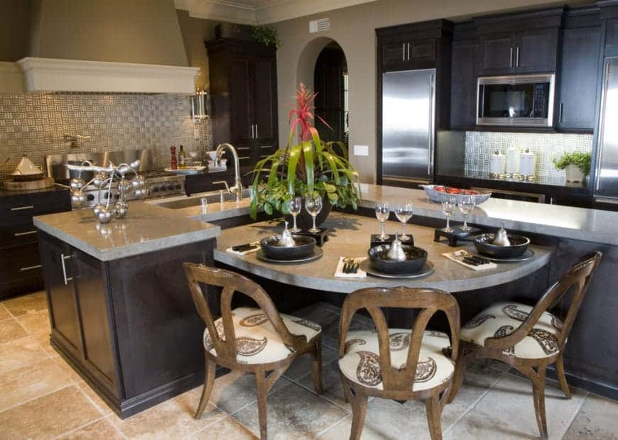 This kitchen features dark wood cabinetry with gray marble countertop. The space outside the peninsula is maximized by placing a built-in counter with seating for a more functional design.