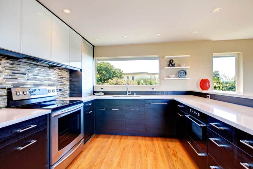Modern kitchen accented with striking multi-colored backsplash tiles and surrounded by a two-tier peninsula.
