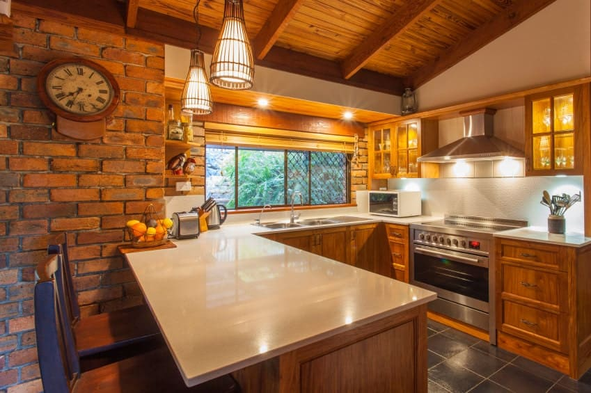 Cozy kitchen features brick walls designed with a French clock. It complements the wood stained cabinets topped with white marble counter. A pair of pendant lights illuminate the peninsula with two seating.