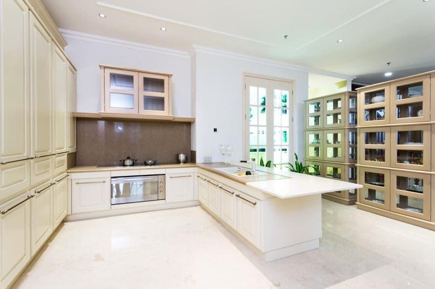 Bright kitchen with white and cream cabinetry accented with brown tile backsplash. It has two display cabinets across the peninsula serving as a divider to the room.