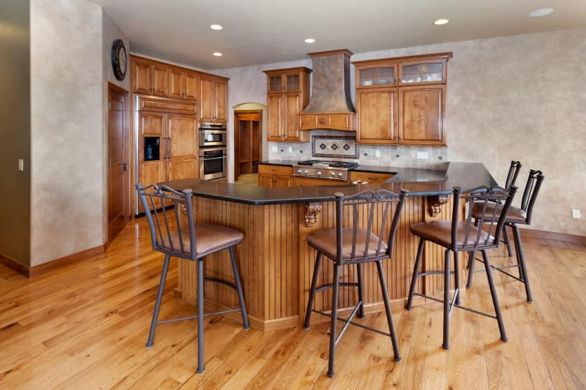 Warm kitchen showcasing a curved peninsula topped with black granite raised counter surrounded with metal chairs. It has hardwood flooring that complements with the wood cabinetry.