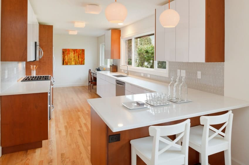 Gorgeous two-toned kitchen designed with an orange wall art piece mounted on the white wall. It includes white with wood accent cabinetry and gray patterned backsplash.