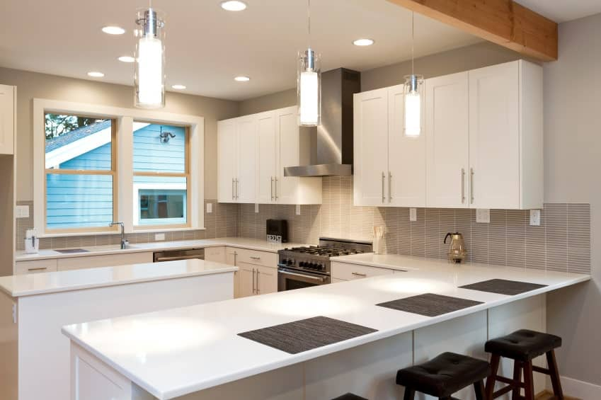 Sleek white kitchen illuminated by modern pendant lights that hung over the peninsula with black bar stools.