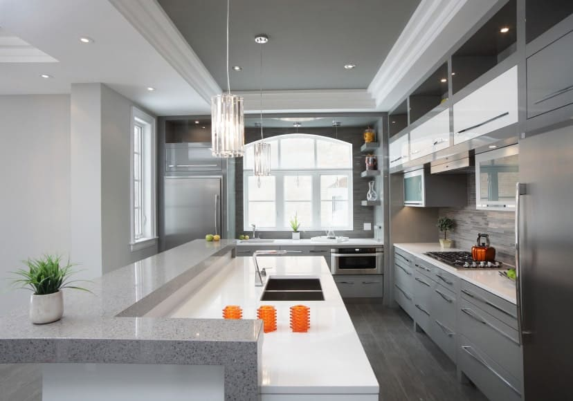 A pair of elegant glass pendants that hung from a tray ceiling lit the gray kitchen. It has a white kitchen counter lined with a thin raised marble countertop.