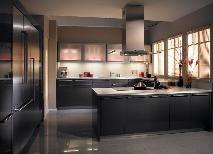 Dark kitchen features upper front glass cabinets and black lower cabinetry on a gray tiled flooring. It has a white countertop peninsula fitted with a built-in cooktop beneath a stainless steel vent hood.