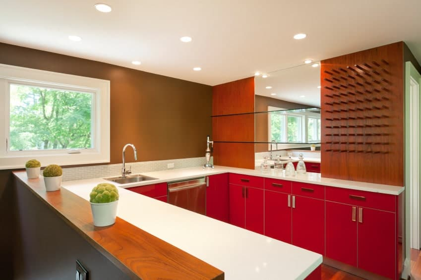 A lively kitchen that's bursting in bold colors. It includes red cabinetry topped with pearl white granite and mini subway tile backsplash.