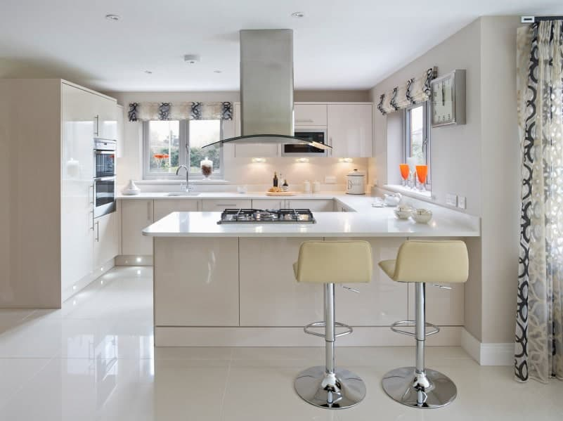 Kitchen with white cabinetry and glass windows covered by patterned roman shades. A pair of cream bar stools sit on the white peninsula fitted with built-in cooktop.