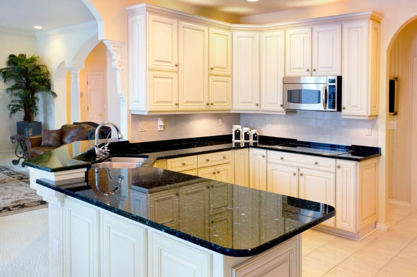 Clean white kitchen beautifully contrasted with black marble countertop. It is fitted with a stainless steel sink and chrome fixtures.