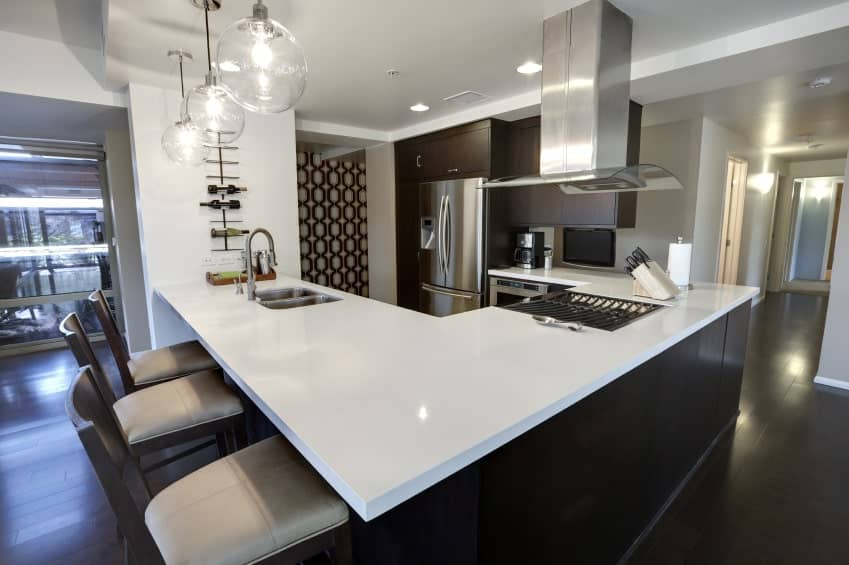 Glass globe pendant lights illuminate this kitchen with dark wood cabinetry that complements with the hardwood flooring. It is contrasted by an absolute white marble countertop.
