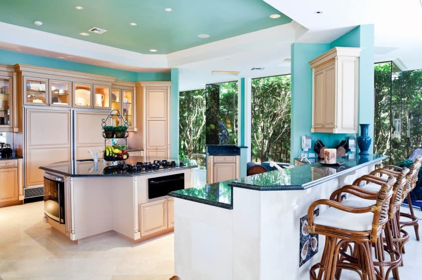 Charming kitchen features blue painted walls and glass windows overlooking a serene outdoor view. It includes an octagonal breakfast island and two-tier peninsula lined with rattan chairs.