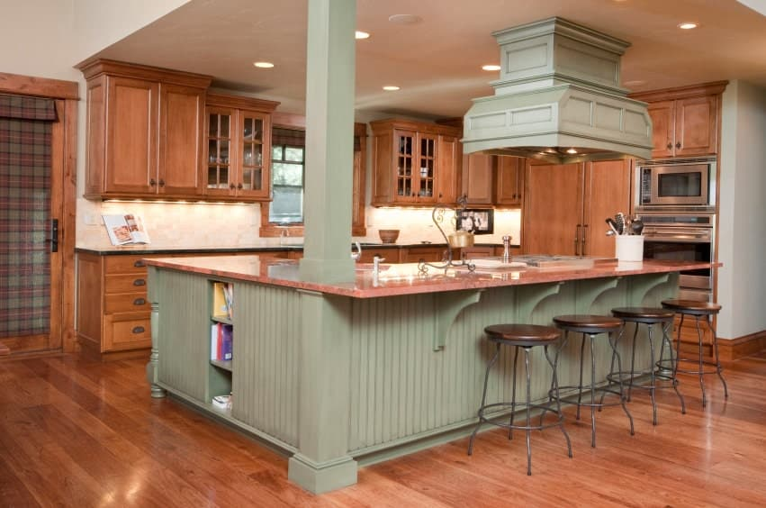 A wood fitted kitchen accented by sage green range hood and shiplap peninsula topped with terracotta marble counter.