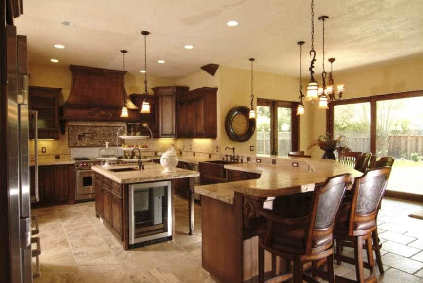 Classic kitchen designed with a wall clock and vintage pendant lights that hung over a breakfast island and peninsula.
