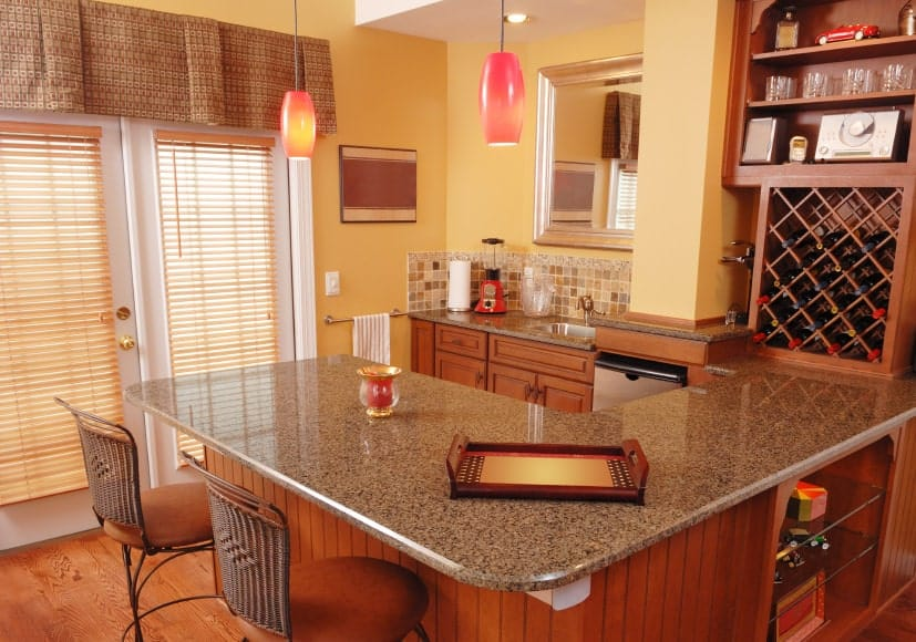 Simple kitchen features mosaic tiles backsplash and built-in wine rack fixed above a marble countertop. A pair of pink pendant lights hung over the peninsula with round counter chairs.