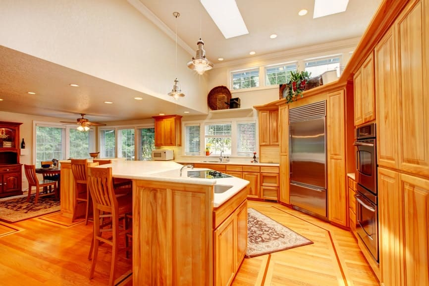 Gorgeous kitchen with a unified wooden look. It has hardwood flooring topped with vintage rugs and glass windows covered with blinds.