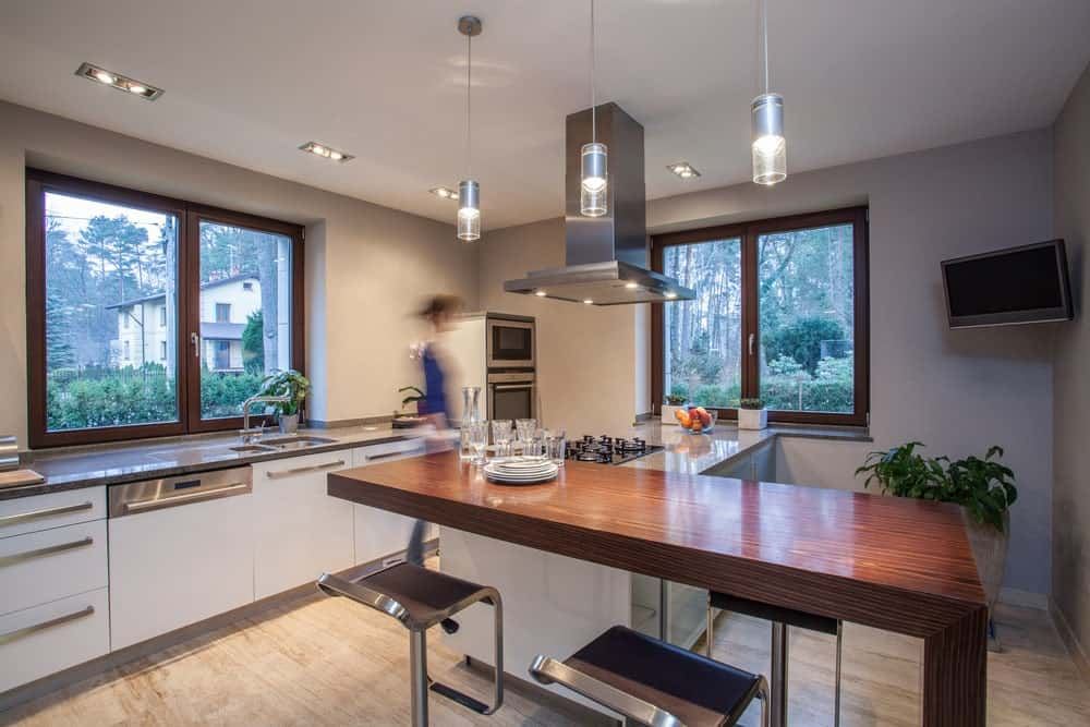 Glass pendant lights illuminate the wooden peninsula with metal chairs in this white kitchen. It includes glazed windows overlooking the outdoor view.