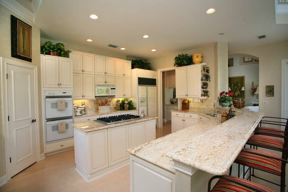 White kitchen featuring a raised peninsula with marble countertop and striped chairs. It has a central kitchen island fitted with a cooktop.