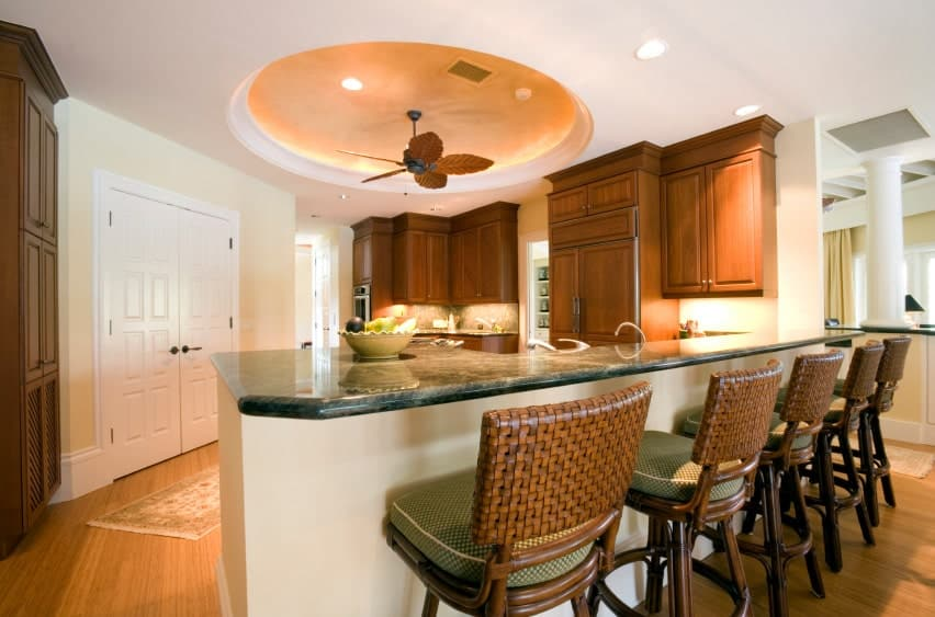 This kitchen is decorated with a unique leaf design ceiling fan that hung from a round tray ceiling. It has wooden cabinetry and white peninsula topped with black marble.